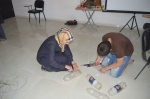 Shaima and our student, Ahmed, prepare the bottles for paint.