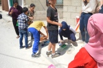 Our student, Ragad, leads the students in spray painting the bottles.